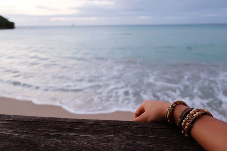 Cropped hand on pier at beach