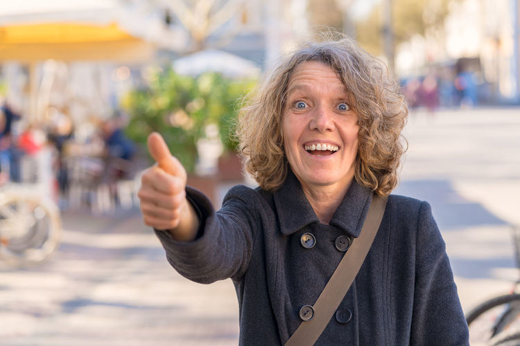 Portrait of smiling mature woman gesturing thumbs up in city