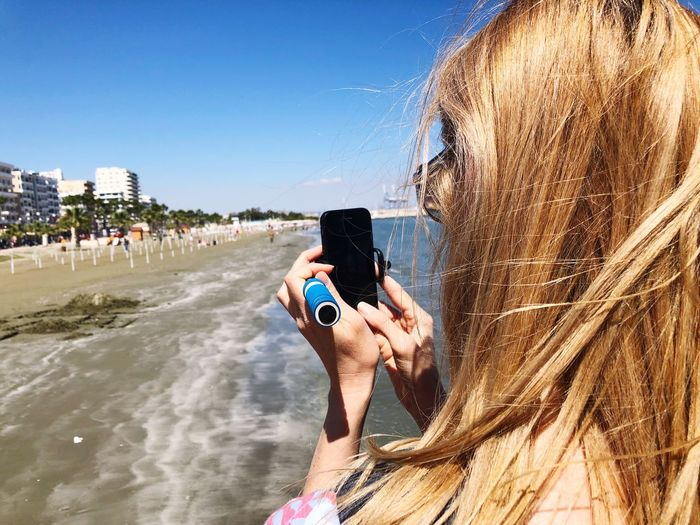 Close-up of woman with blond hair using mobile phone at beach