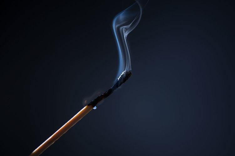 Close Up Of Burnt Matchstick Against Black Background