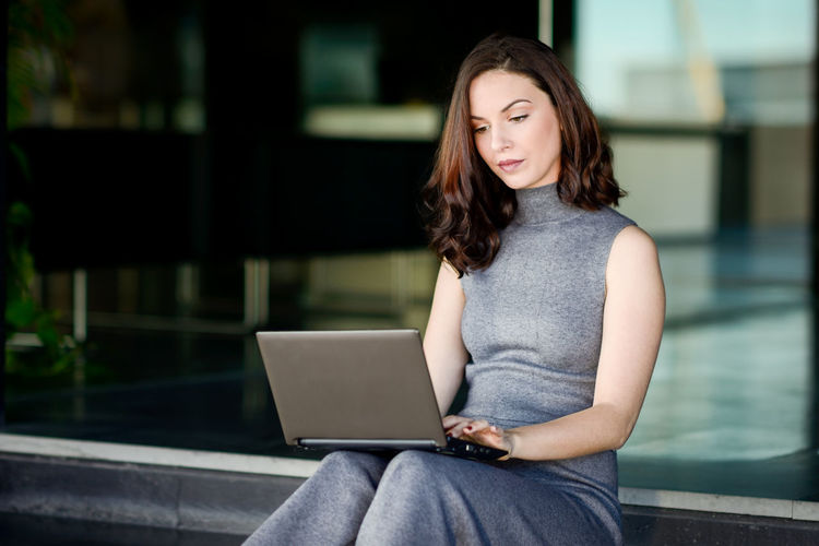 Young Woman Using Laptop While Sitting On Steps