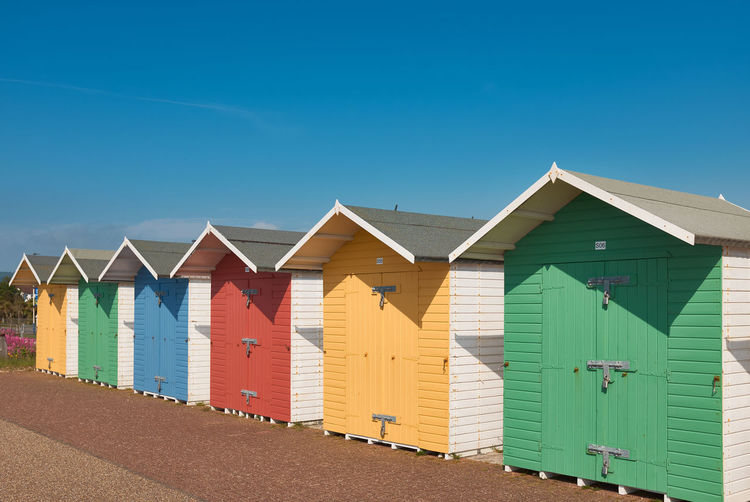 Beach huts against buildings against blue sky