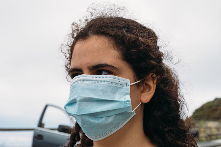 Portrait of a beautiful young woman wearing face mask against sky