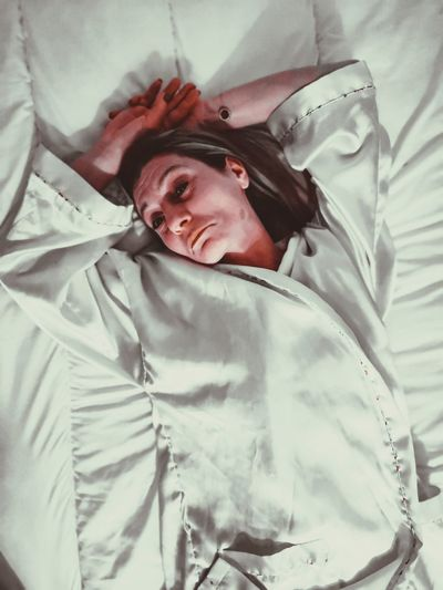 Portrait of woman lying on bed