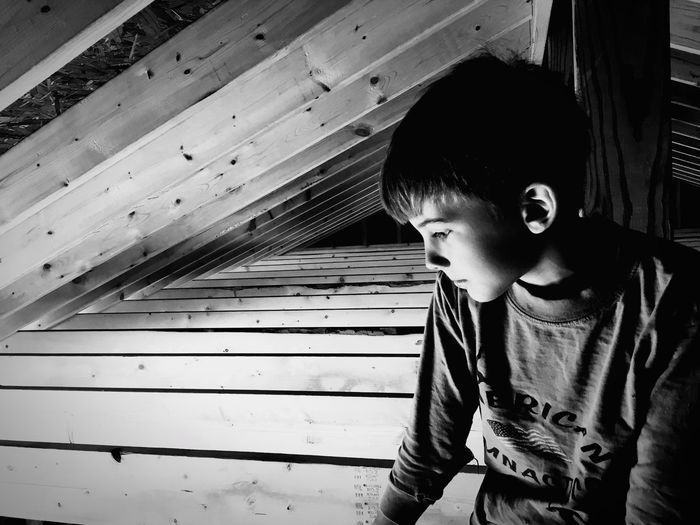 Boy looking down while sitting on roof beam