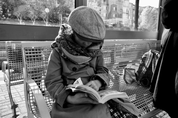 Girl in warm clothing reading book while sitting on bench