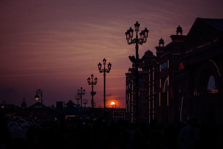 Silhouette people against illuminated orange sky during sunset
