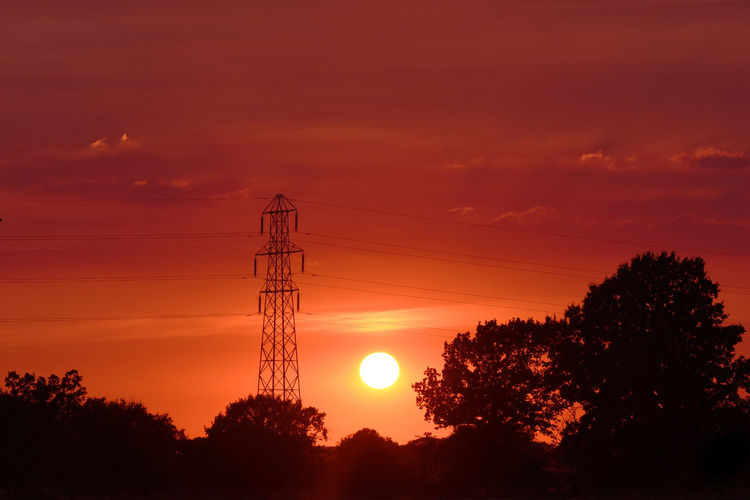 Silhouette trees and electricity pylon against romantic sky at sunset