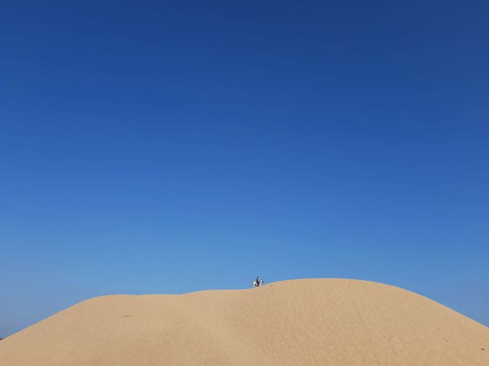 View of man riding horse on sand dune against clear sky