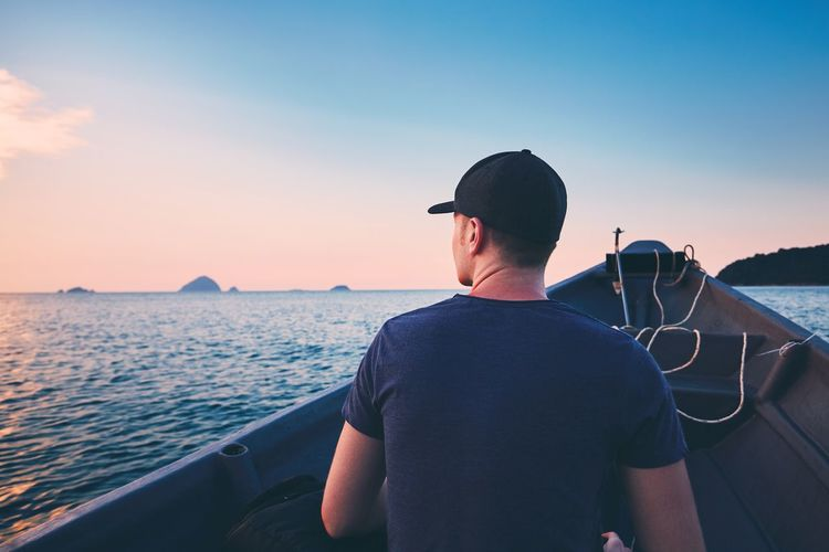 Rear view of man traveling in boat on sea during sunset
