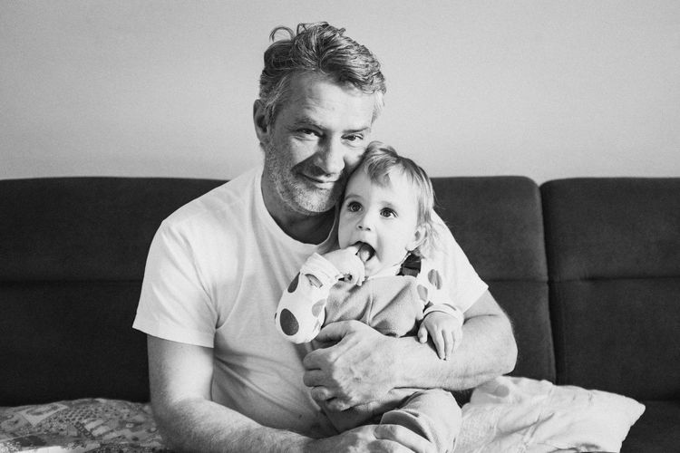 Portrait of smiling man sitting with toddler son on sofa at home
