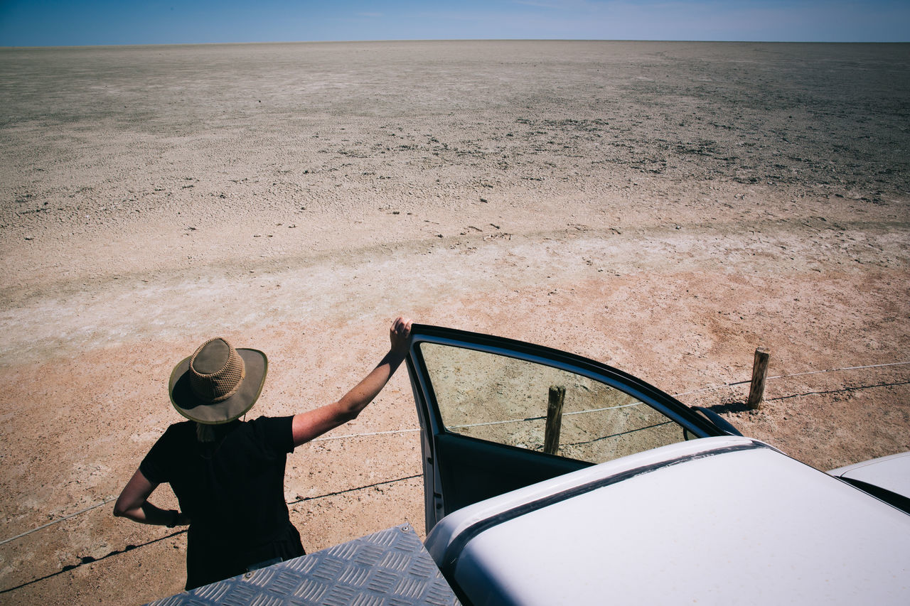 High angle view of person standing by off-road vehicle in desert on sunny day