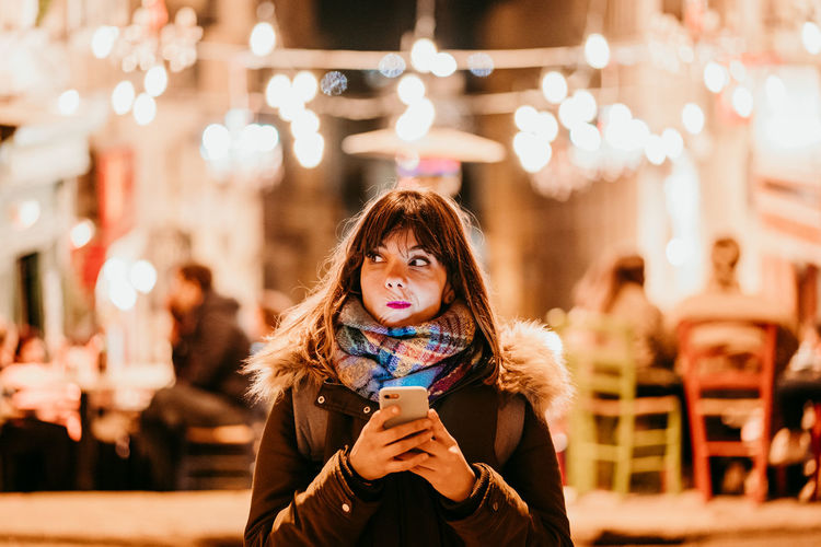 Portrait of young woman using mobile phone in winter
