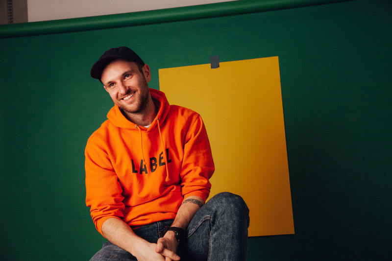 Portrait of a smiling young man sitting against wall