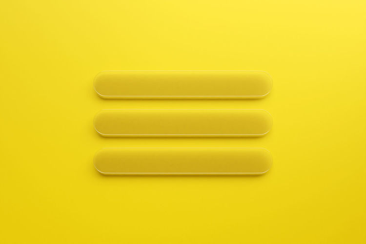 Directly above shot of yellow buttons against white background