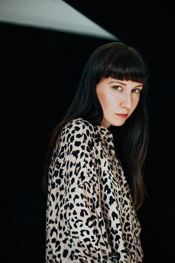Portrait of beautiful woman standing in darkroom