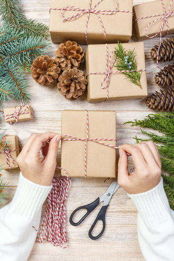 High angle view of woman packing gift box
