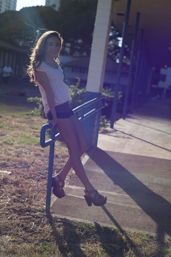 Full Length Of Young Woman Sitting On Metallic Railing During Sunny Day