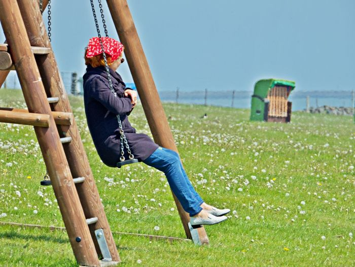 Side view of woman sitting swing over grassy land