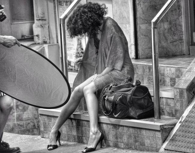 Fashion Model Sitting On Step In City