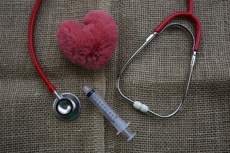 Stethoscope, syringe, and a heart shape on a brown sack background with a text Health Care. Medical, Healthcare and Wellness concept. Doctor  Medical Equipment Wellness Close-up Directly Above Healthcare And Medicine Heart Shape High Angle View Indoors  Medical Medical Instrument Medical Supplies Music Needle Stethoscope  Still Life Syringe Textile