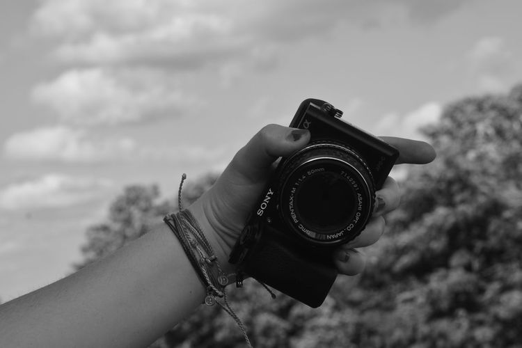 Close-up of hand holding camera against sky