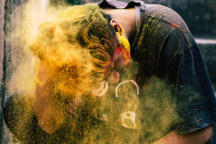 Young man covered with powder paint