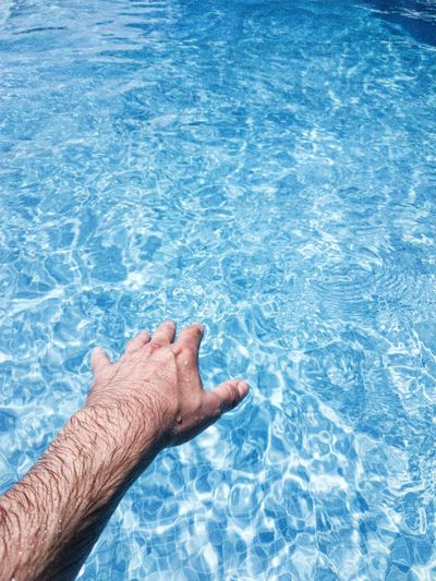 Low section of man on blue water in swimming pool