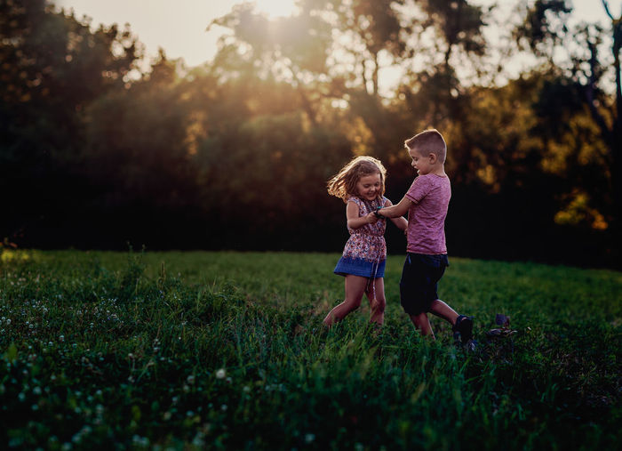 Plant Ring Around The Rosie Siblings Bonding Boys Casual Clothing Childhood Day Field Friendship Full Length Girls Grass Leisure Activity Nature Outdoors People Real People Sky Sunlight Togetherness Tree Two People