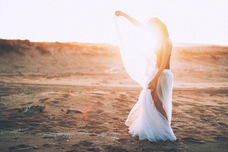 Woman on sand at beach against clear sky