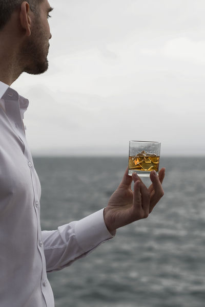 Whiskey in hand by the sea vertical portrait Alcohol Bourbon Clean Cruise Dram Glass Golden Hand Human Element Ice Lifestyle Luxury Portrait Rocks Sailing Scotch Sea Shirt Tequila Wealth Whiskey White Yacht