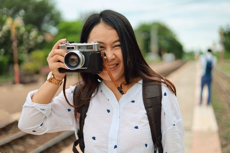 Camera - Photographic Equipment Photography Themes Technology One Person Activity Photographing Front View Focus On Foreground Young Adult Leisure Activity Portrait Women Holding Adult Lifestyles Young Women Casual Clothing Standing Occupation Hairstyle Hair Outdoors Photographer