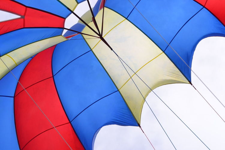 Low Angle View Of Colorful Parachute Flying In Sky