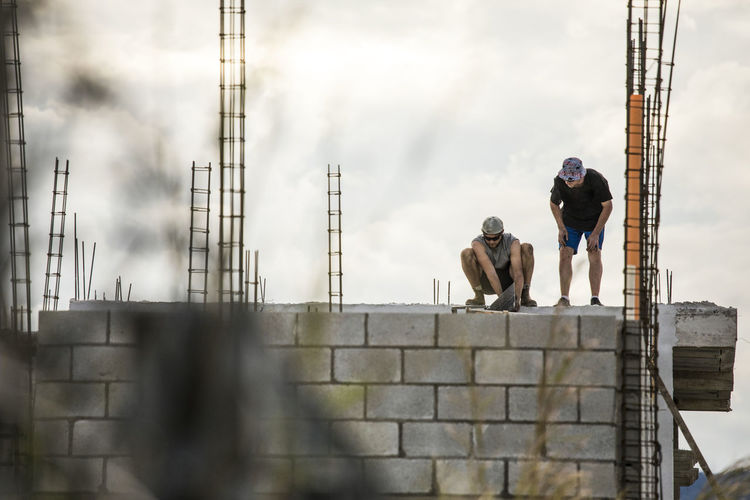 Men working at construction site against sky