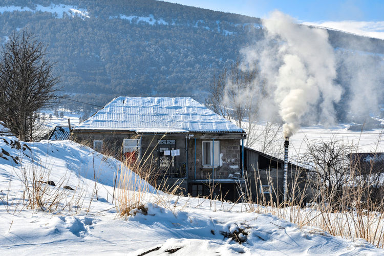 Smoke emitting from snow covered building against mountain