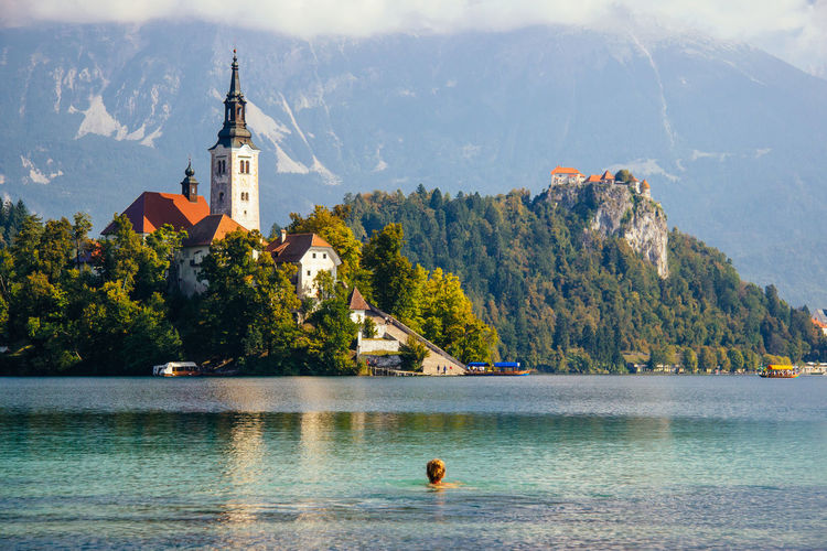 View of woman swimming in lake bled