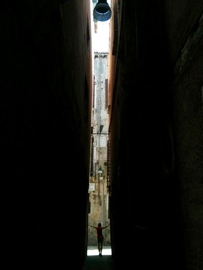 Silhouette people in alley amidst buildings in city