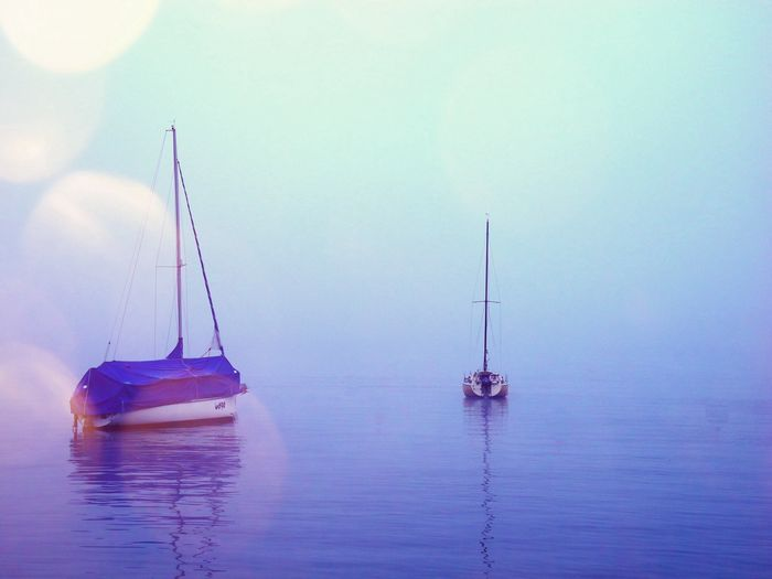 View of two boats in calm sea against clear sky