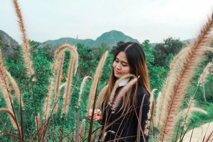 Beautiful young woman with plants in background against sky
