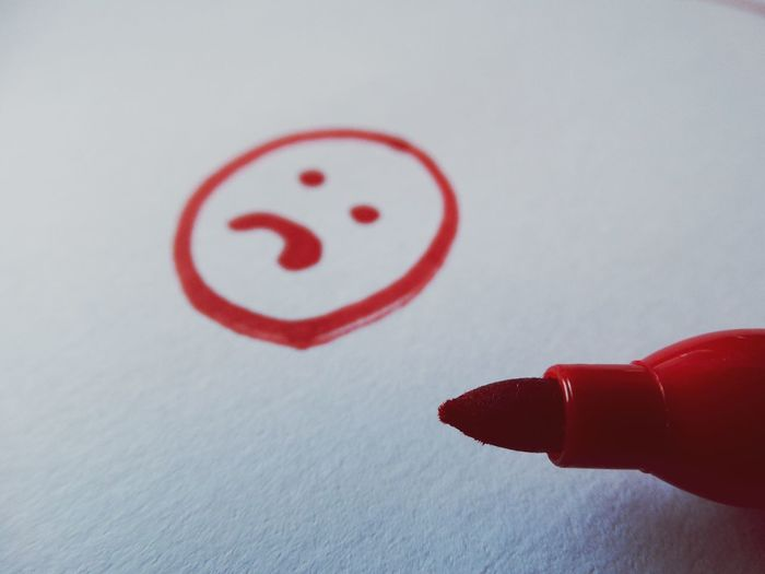 Close-up of sad anthropomorphic face with felt tip pen on paper