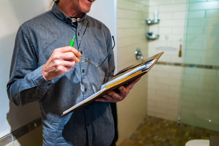 Midsection of man holding clipboard at bathroom