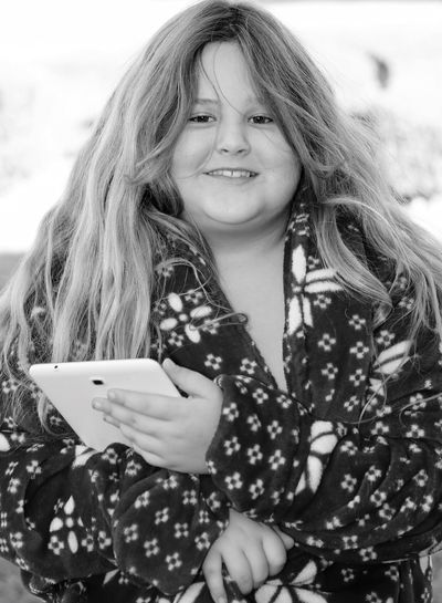 Portrait of smiling overweight girl holding smart phone