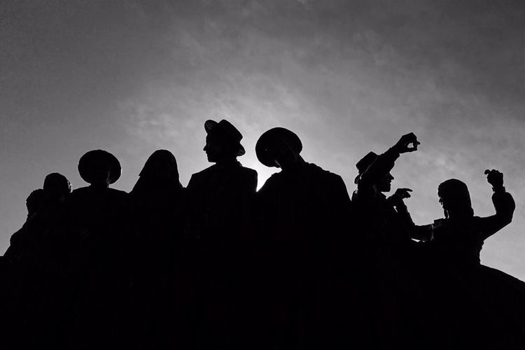 Low angle view of silhouette friends against sky