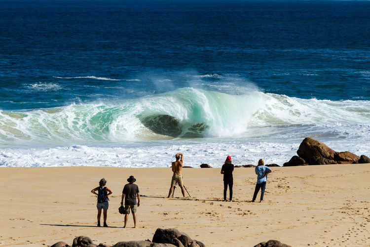 Rear view of people on beach watching waves