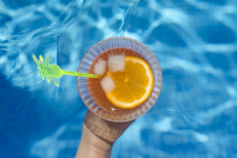 Cocktail by the pool Aperitivo  Aperol Blue Bokeh Close-up Day Drink Food Food And Drink Freshness Holding Human Body Part Human Hand One Person Outdoors People Ready-to-eat Real People Refreshment Spritz Summer Sweet Food Swimming Pool Water