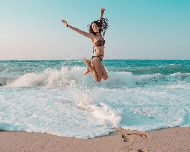 Full length of woman enjoying at beach against sky