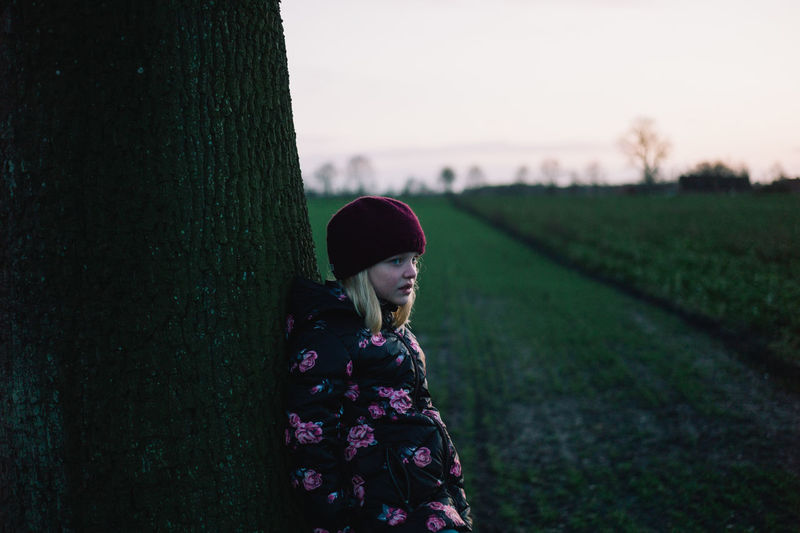 Girl standing by tree on field against sky