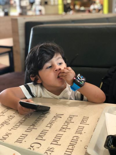 Cute boy with phone sitting in restaurant