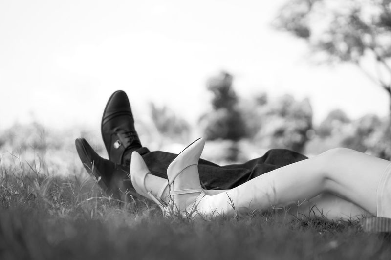 Low section of couple lying on grass in park
