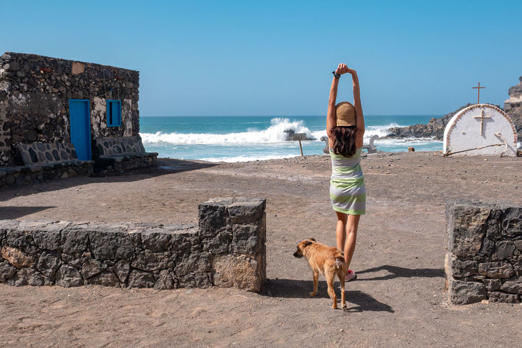 Sea Water Dog Canine Beach One Animal Full Length Animal Real People Animal Themes One Person Domestic Animals Sky Mammal Land Pets Day Nature Domestic Arms Raised Human Arm Horizon Over Water Outdoors Pet Owner